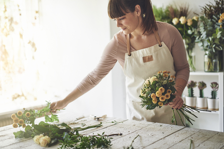 Smiling female florist working at a table in her flower shop arranging a bouquet of roses Imagens