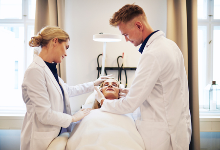 Two doctors discussing a cosmetic surgery procedure on the face of a mature woman lying with her eyes closed on a table in a clinic Stock Photo