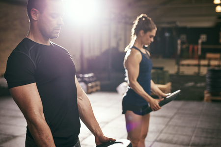 Sportive man and woman holding heavy weight discs and doing exercised in spacious light gym. Stock fotó
