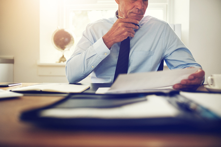 Mature executive wearing a shirt and tie sitting at his desk in an office reading through paperwork