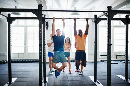 Two fit young men having a pullups competition in a gym with a diverse group of friends cheering them on in the background