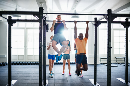 Two fit young men having a friendly pullups competition in a gym with a diverse group of friends cheering in the background