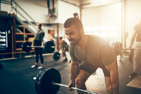 Fit young man in sportswear straining to lift heavy weights while working out in a gym class Stock Photo