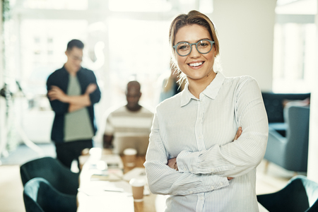 Young businesswoman smiling confidently while standing with her arms crossed in an office with colleagues working in the background Stock fotó