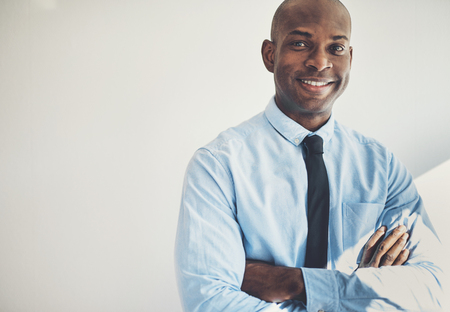 Smiling African businessman wearing a shirt and tie standing with his arms crossed in his home office Stock Photo