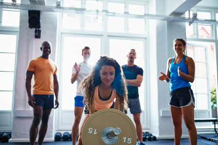 Focused young woman straining to lift a barbell with friends cheering her on in the background while enjoying a workout at the gym