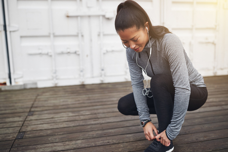 Smiling young Asian woman in exercise clothing kneeling on the ground outdoors tying up her shoelaces before going jogging