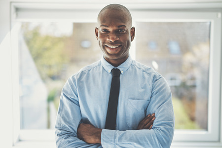 Smiling African businessman wearing a shirt and tie standing confidently with his arms crossed in his home office