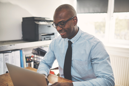 Smiling African businessman wearing a shirt and tie sitting at a desk working online with a laptop from his home office Stock Photo