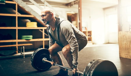 Focused mature man in sportswear preparing to lift weights while working out in a gym Stock Photo