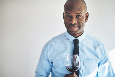 Smiling mature African man in a shirt and tie drinking a glass of red wine