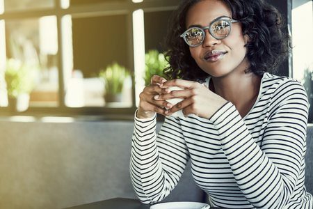 Smiling young African woman wearing glasses sitting alone at a table in a cafe drinking a fresh cup of coffee