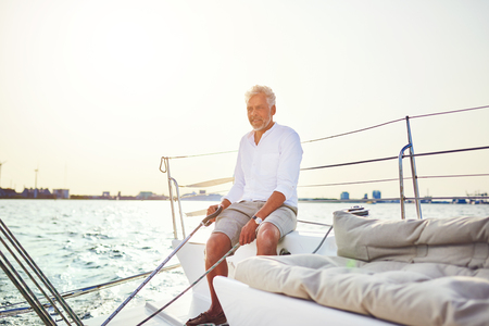 Mature man sitting on the deck of a boat while out for a sail along the coast on a sunny day