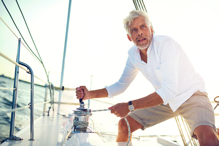 Mature man standing on the deck of a boat working a winch while out for a sail on a sunny afternoon Stok Fotoğraf