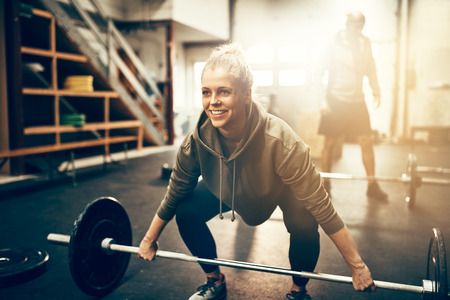 Fit young woman in sportswear smiling while preparing to lift heavy weights during a workout session in a gym
