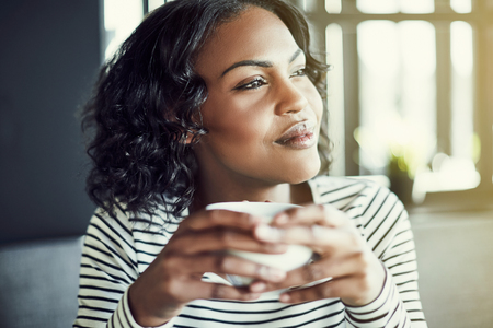 Smiling young African woman sitting alone at a table in a cafe enjoying a fresh cup of coffee and looking out through window