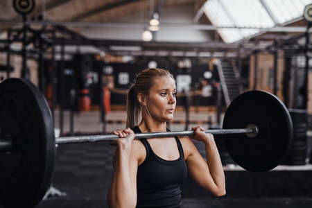 Fit young blonde woman in workout clothing straining while lifting heavy weights alone in a gym