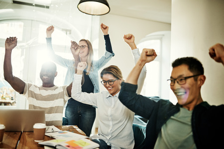 Excited group of diverse businesspeople cheering during a meeting while working together in a modern office Foto de archivo