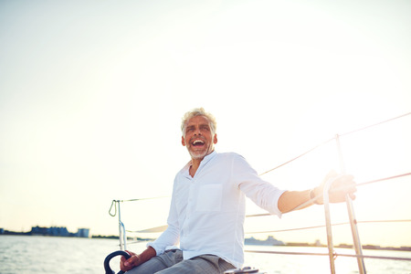 Mature man sitting on the deck of his yacht laughing while enjoying the day sailing on the open ocean on a sunny afternoon Stockfoto