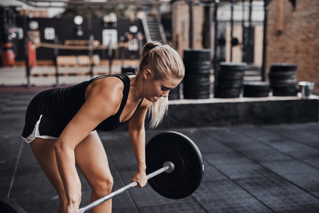 Fit and focused young blonde woman in workout clothing lifting barbells while exercising alone in a gym
