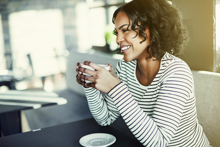 Laughing young African woman sitting alone at a table in a cafe enjoying a freshly brewed cup of coffee Stock Photo
