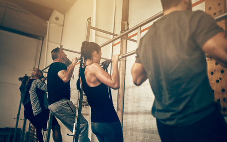 Group of fit people in sportswear doing chin ups together during an exercise class at the gym
