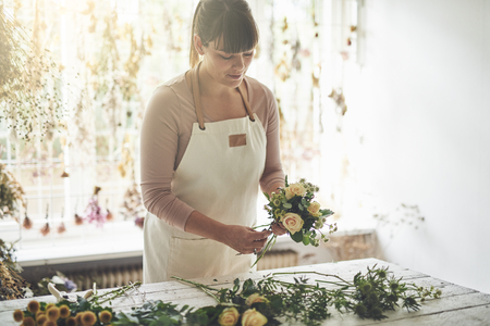 Young female florist putting together a bouquet of roses while working at a table in her flower workshop