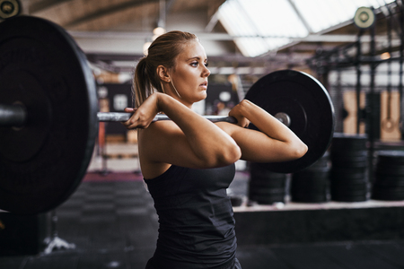 Fit young blonde woman in workout clothing straining to lift heavy weights during strength training in a gym Stock Photo
