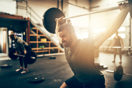 Fit and focused young man straining to lift heavy weights over his head during a workout session in a gym