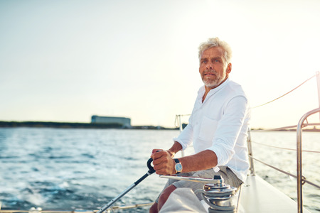Mature man sitting alone on the deck of his yacht sailing on the open ocean on a sunny afternoon
