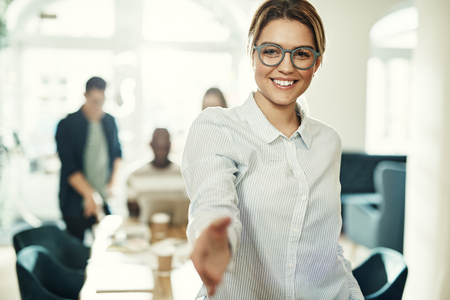 Smiling young businesswoman extending a handshake while standing in an office with colleagues at work in the background