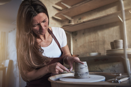 Female artisan creatively sculpting a piece of clay turning on a pottery wheel while sitting in her ceramic studio