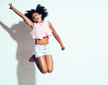 Ecstatic young African girl with long curly hair shouting and jumping in the air with her arm raised against a white background