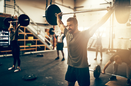 Fit young man lifting heavy weights above his head during a workout class in a gym