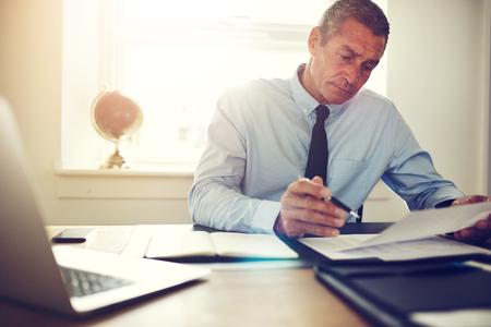 Koncentruje się dojrzały biznesmen ubrany w koszulę i krawat, czytając dokumenty, siedząc przy biurku w biurze