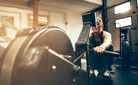 Fit young woman in sportswear exercising on a rowing machine during a workout session in a gym Stock Photo