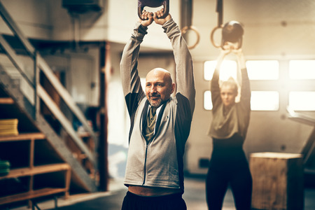 Fit mature man in sportswear smiling and swinging a weight during an exercise class in a gym Stok Fotoğraf - 96976124