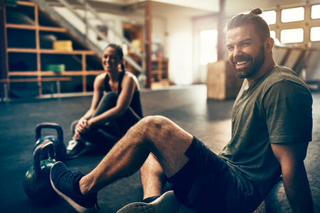 Fit people in exercise gear sitting together on the floor of a gym laughing together after a workout Фото со стока