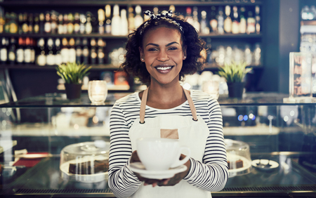 Smiling African barista standing at the counter of a trendy cafe holding up a fresh cup of coffee