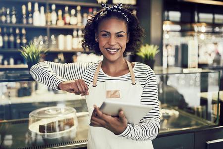 Glimlachende jonge Afrikaanse ondernemer die een schort dragen die zich voor de teller van een trendy koffie bevinden die een digitale tablet gebruiken Stockfoto - 96976156
