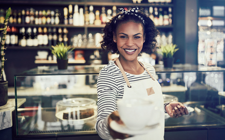 Smiling young African barista standing in a trendy cafe holding up a fresh cup of coffee
