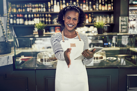 Friendly young African entrepreneur standing in her trendy cafe holding a digital tablet and extending her arm to shake hands