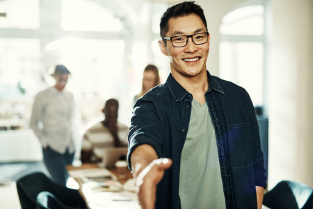 Smiling young Asian businessman extending a handshake while standing in an office with colleagues working in the background Stock Photo