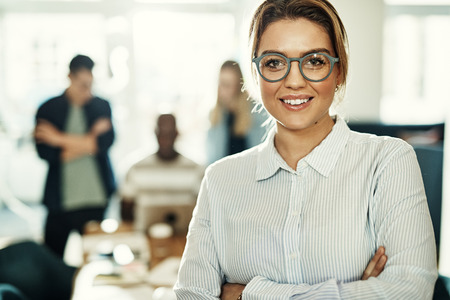 Confident young businesswoman standing with her arms crossed in a modern office with colleagues working in the background