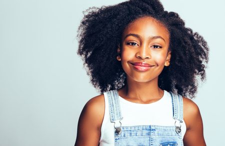 Cute young African girl with long curly hair wearing dungarees and smiling while standing alone against a gray background
