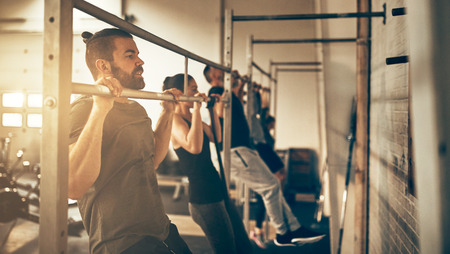 Group of fit people in sportswear doing chin ups while working out together at the gym