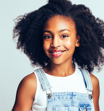 Young African girl with long curly hair wearing dungarees and smiling confdiently while standing against a gray background Stock Photo