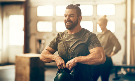 Fit young man in sportswear smiling and lifting weights during an exercise class in a gym