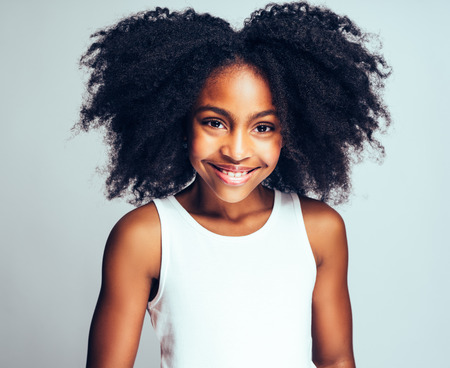 Happy young African girl with long curly hair smiling confidently while standing alone against a white background