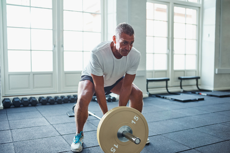 Senior man in sportswear standing alone in a gym focused on lifting weights during a workout